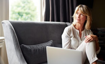 Mature Woman Using Laptop on Sofa